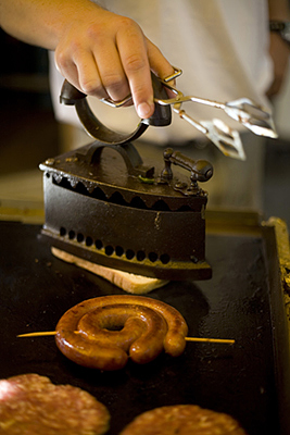 Hungary - Pecs - A chef irons a piece of fried bread on a griddle with a sausage at a food stall