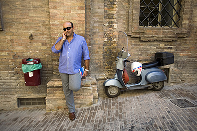 Italy - Urbino - A man talks on his mobile telephone while leaning against a wall next to his Vespa