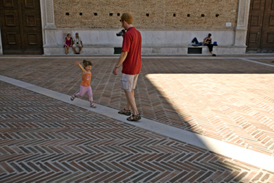 Italy - Urbino - A tourist videos his little girl running down a path outside the Palazzo Ducale