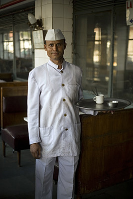 India - New Delhi - A waiter holding a tray with a coffee cup and spoons in the Indian Coffee House, Baba Kharak Singh Marg