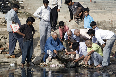 India - Delhi - A group of men come to perform a ritual of casting ashes into the Yamuna River, after a cremation of a family member. Nigambodh Ghat, New Delhi, India