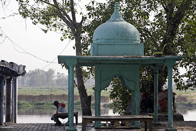 India - Delhi - An old man sits by a temple at the Nigambodh Ghat on the banks of the River Yamuna in New Delhi India