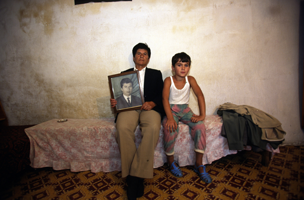 Albania - Lepurush Village - Selman Brahim has been living as a man for 40 years after the family's eldest son died. In the Albanian tradition of the Avowed Virgin ('Virgjineshe' or 'Sworn Virgins'), authorised by the Kanun of Lek (an ancient system of laws) she/he now leads the family as a man. She/he is seen here with her sister's grandchild and a picture of him/her as a younger person