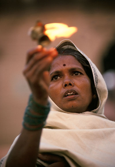India - Varanasi - Radha, a low caste Hindu priestess, worships at the River Ganges in Varanasi, India