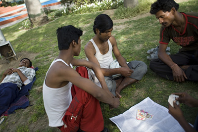India - New Delhi - Men play cards on a traffic island in New Delhi, India whilst one of their friends sleep. The traffic islands in the centre of the city often have manicured lawns and are well cared for. Many people sleep here at night but in the daytime they are used as small parks by workers
