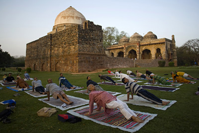 India - New Delhi - A yoga class in Lodi Gardens in front of the Bara Gumbad Tomb