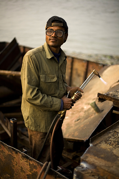 Bangladesh - Chittagong - A man dismantles a boat with a blow torch and hammer on the banks of the Karnaphuli River beneath the Kalurghat Bridge, Chittagong, Bangladesh