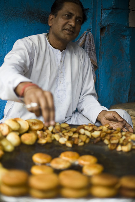 India - Delhi - A street vendor frying potato cakes on a stall