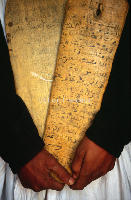 Mauritania - Chinguetti - A man hold a wooden lah covered in Koranic inscriptions