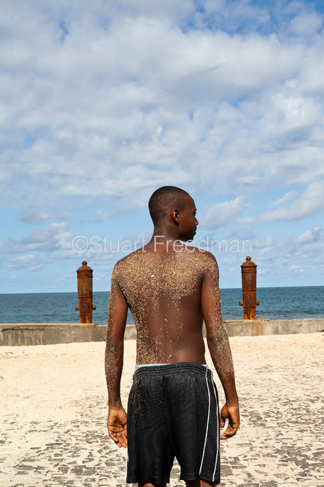 São Tomé and Principe - São Tomé - A boy with a sand covered back on the Marginal 12 Julho, Sao Tome