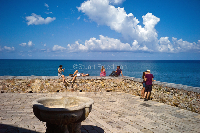Italy - Cefalu - Tourists photograph, chat and kiss on the sea wall