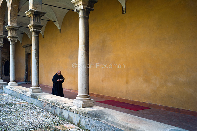Italy - Palermo - A priest reads as he walks through the cloisters in the courtyard of the St Augustino church