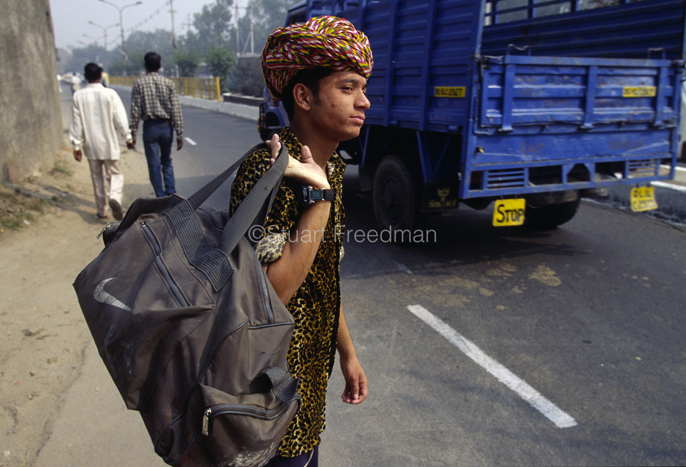 India - New Delhi - A boy on his way to perform his magic act at a wedding waits for a lift by the side of the road