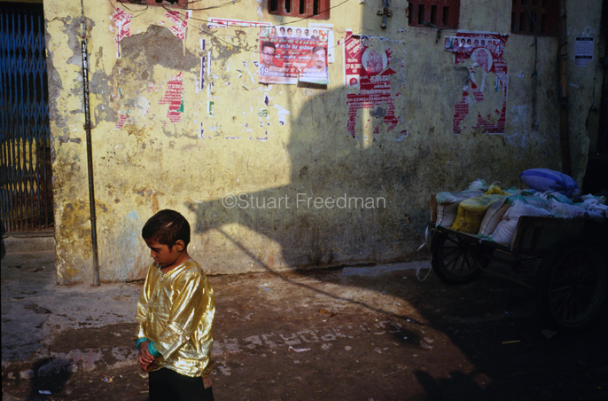 India - New Delhi - A performers son in a gold shirt, Shadipur Depot,