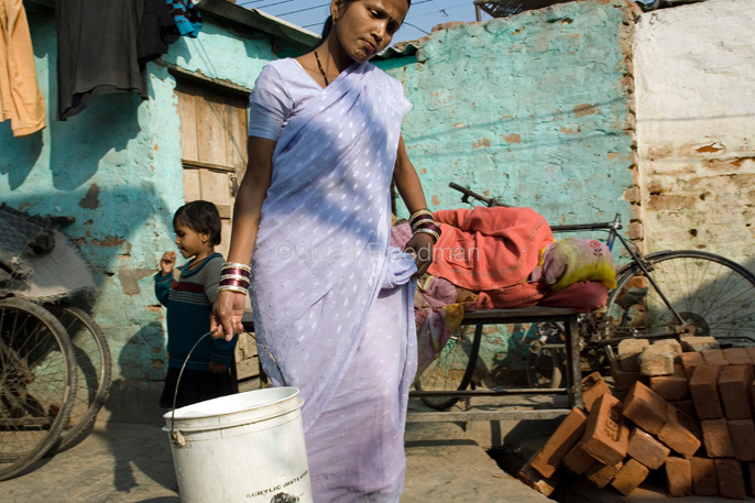 India - Delhi - A woman carries water delivered by tanker back to her home in the slum of Kusumpur Pahari. The slum, built more than thirty years ago has no running water or sewage facilities. The only water supply come from the Municipal  JAL Board water trucks that visit several times a day. The deliveries are supposed to be free but in reality, residents must pay bribes to have the water delivered.