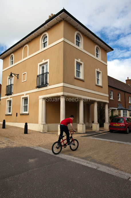 UK - Dorset - A boy rides his bicycle past a traditionally styled building in Poundbury. Poundbury on Duchy of Cornwall land is Prince Charles' attempt to create an urban extension to Dorchester famed for Its pastiche of traditional architecture.