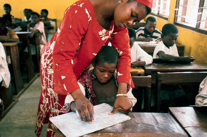 Ghana - Tamale - A street child is helped to read in a school by a teacher in a school run by the Youth Alive project