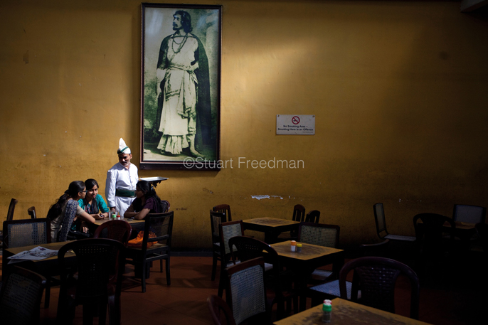 India - Kolkata - A waiter serves schoolgirls beneath a portrait of Rabindranath Tagore in the Indian Coffee House