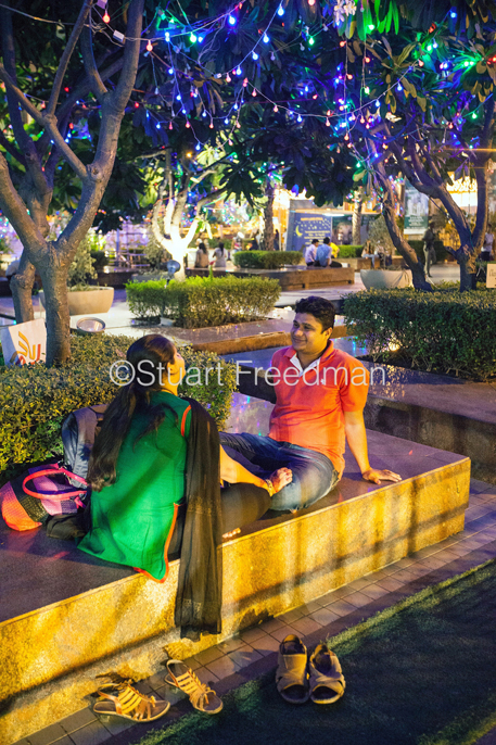 India - Delhi - A romantic couple sit in the gardens of the Ambiance Mall, Saket,