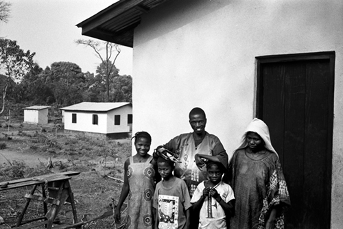 Hassan Fufona and his family outside their resettlement house