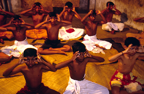 Young students at the Kalamandalam practice eye exercise at dawn. Kathakali uses very intricate eye and hand movements to communicate with the audience