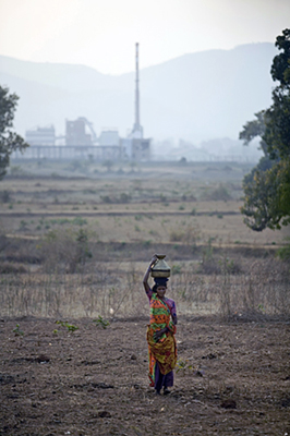A woman carries a pot of water from a stream in front of the Vedanta plant, Lanjigarh, Orissa