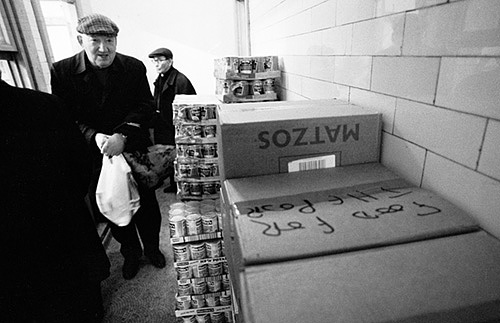 An old man collects his grocery allowance from the Soup Kitchen for the Jewish Poor in Brune Street near Brick Lane.
