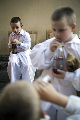 Hungary - Pecs - Boys backstage in traditional costume drink soda from bottles during a folk event