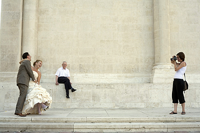 Hungary - Pec - A newly wed couple pose for a photographer by the Bishop's Palace and Saint Peter's Church