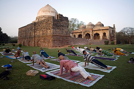 India - New Delhi - An early morning yoga class in Lodi Gardens in front of the Bara Gumbad Tomb