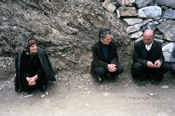 Albania - Thethi - Pashke Sokol Ndocaj sits with the men and a female neighbour in their village. Since the death of her father and brothers, Pashke has lived as a man in the ancient traditions of Avowed Virgins of Albania, where women 'become' men to head the family and renounce their former sex