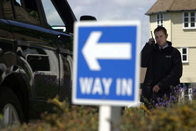 UK - Cirencester - A private Security Guard examines the licence plate of a vehicle outside a Gated Community,