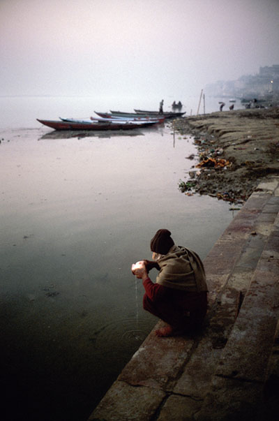 India - Varanasi - A man makes an offering to the Ganges at dawn