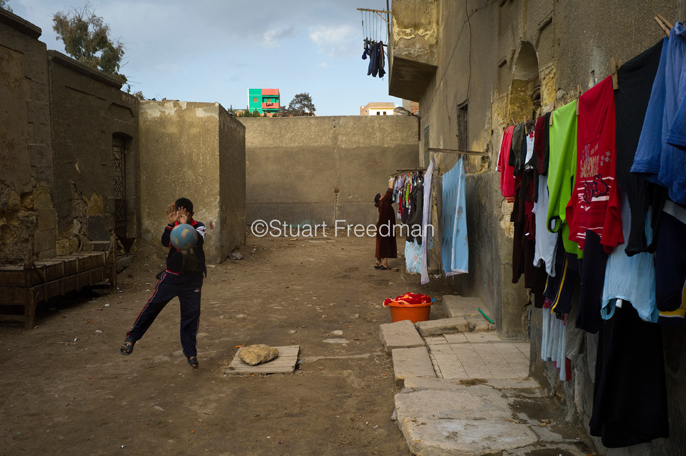 Egypt - Cairo - Boys play football in an alleyway in the Northern Cemetery known as the City of the Dead