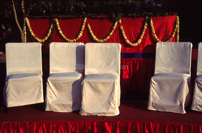 India - New Delhi - A stage set for a wedding with chairs and garlands