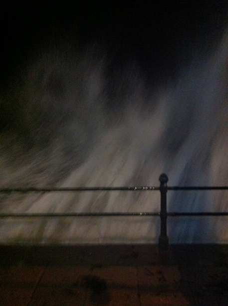 UK - Penzance - A wave breaks over the sea wall