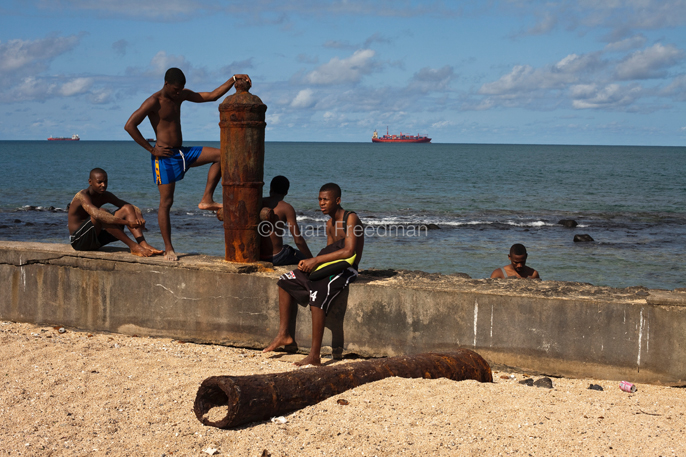 Sao Tome - Sao Tome - Boys sit on the wall of the Avenue Marginal 12 Julho
