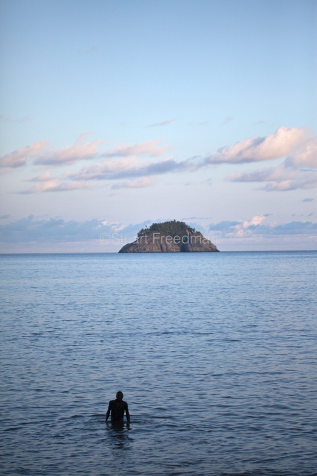 Sao Tome - Sao Tome - Young men swim towards the Isla Sebastao at dusk