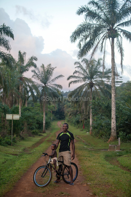 Sao Tome and Principe - Principe - A man poses with his child and his bike, having just ridden out of the jungle