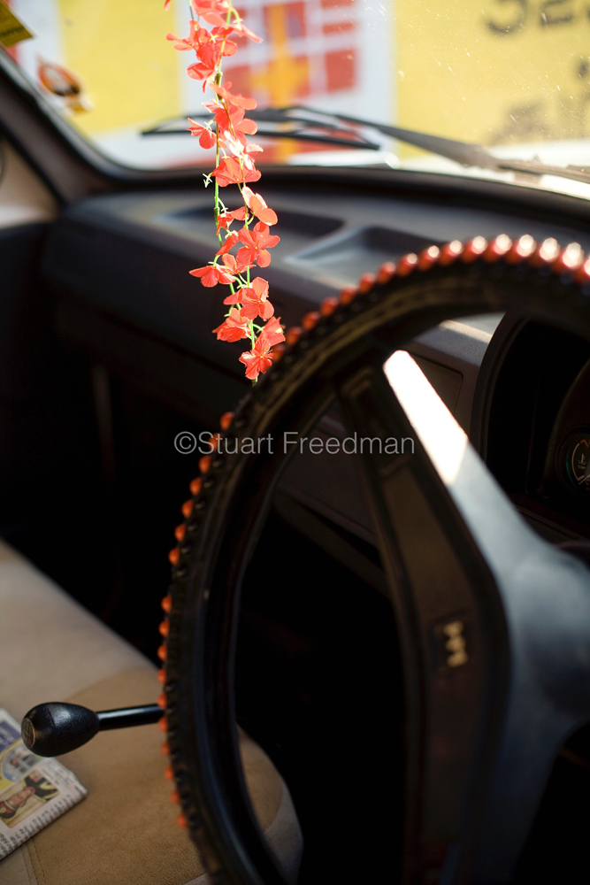 "India - Swamimalai - A garland of flowers hang from the mirror of an Hindustan Ambassador  car in the town of Swamimalai, Tamil Nadu, India.The car, based on a Morris Oxford has been in production since 1948 and is considered as a definitive Indian car and is fondly called ""The king of Indian roads"" and nicknamed the 'Ambi'.."