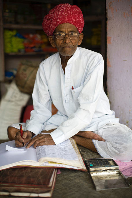 An old man working as a scribe outside a shop in a Jaipur Bazaar, Jaipur, India