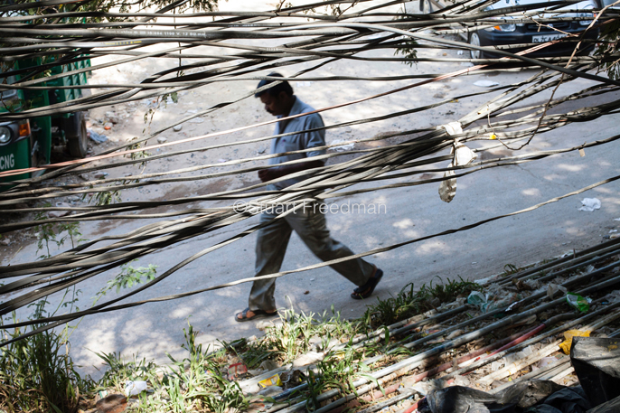 India - New Delhi - A man  seen through a tangle of illegal electricity and water cables in the Munika area.