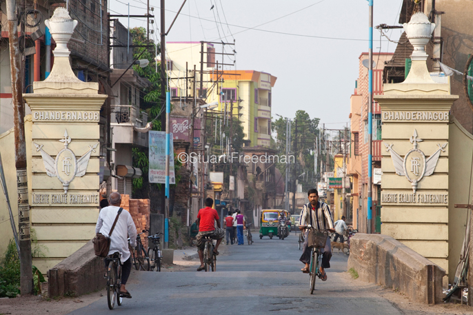 India - Chandernaggar - Traffic passes the gates to the town of Chandannagar bearing the French inscription, Liberte, Egalite, Fraternite. Chandannagar, India