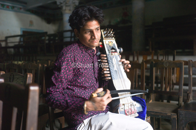 India - Chandannagar - Umesh Mishra, 26 a sarangi virtuoso tunes his instrument before a concert later that night at the Nrityagopal Smriti Mandir